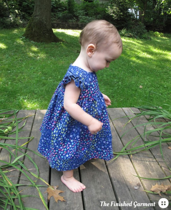 Baby dress made by The Finished Garment using the Geranium Dress sewing pattern from Made by Rae and Floral Meadow fabric from the Storybook Lane collection.